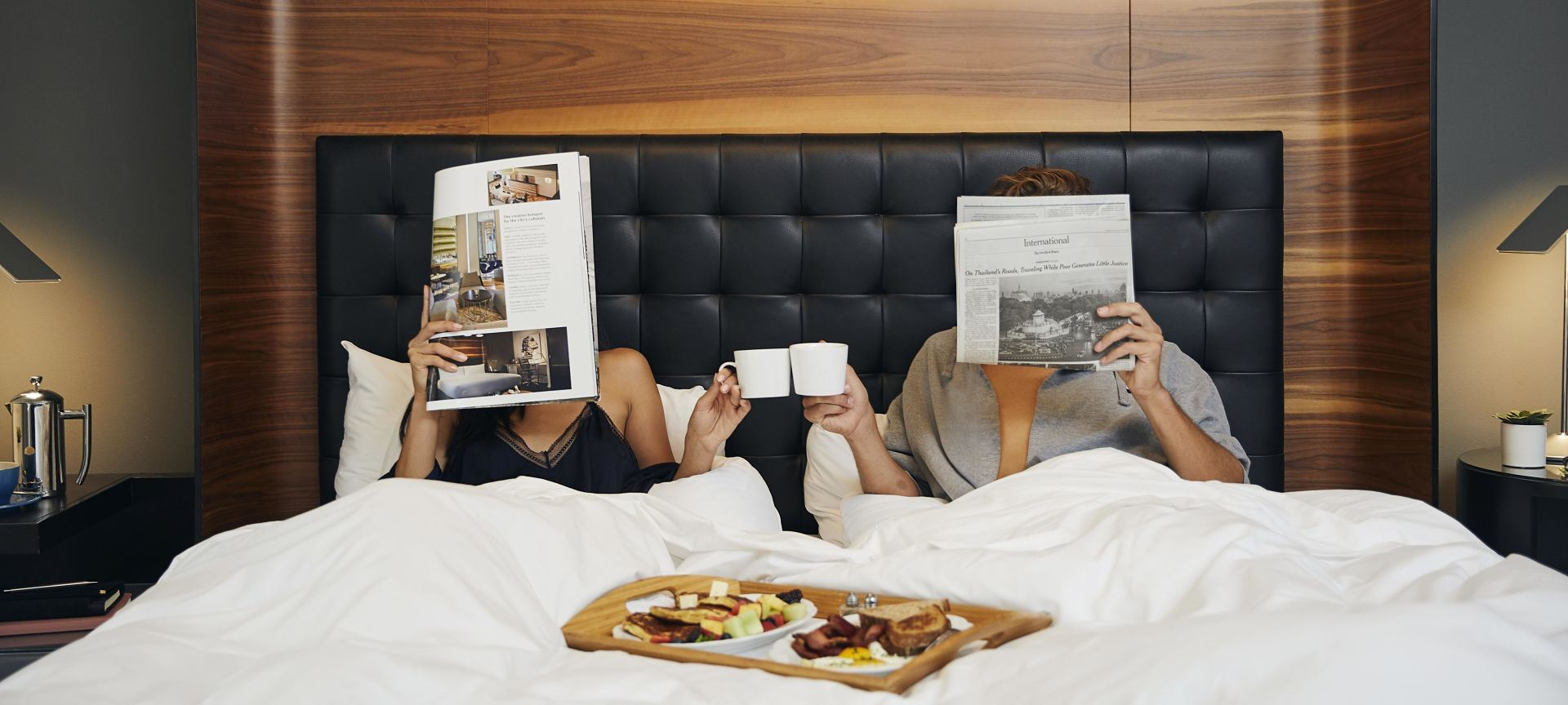 A Couple in Bed with Breakfast and Reading